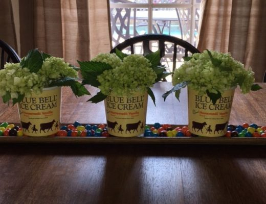 Image of Blue Bell Floral Centerpiece. Centerpiece is three recycled Blue Bell ice cream pint cartons filled with pretty white flowers.