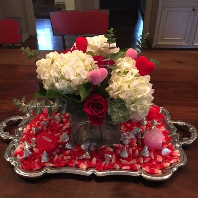Image of a centerpiece with white and red flowers and candy around it.